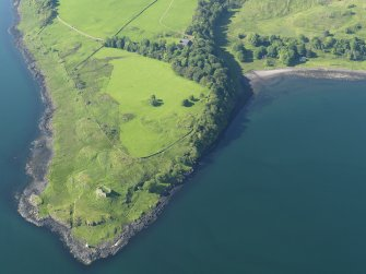 Oblique aerial view of the remains of Ardtornish Castle with the remains of the fish trap in the bay beyond, taken from the SSE.