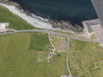 Oblique aerial view centred on the excavated broch and settlement at Old Scatness, Sumburgh, and the visitor attraction, taken from the E.