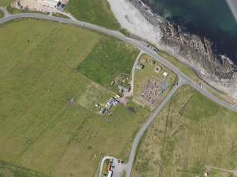 Oblique aerial view centred on the excavated broch and settlement at Old Scatness, Sumburgh, and the visitor attraction, taken from the ENE.