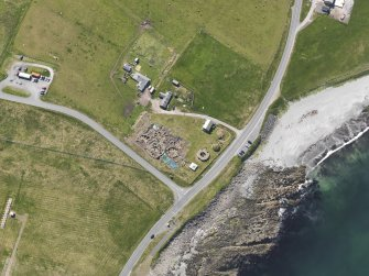 Oblique aerial view centred on the excavated broch and settlement at Old Scatness, Sumburgh, and the visitor attraction, taken from the NNW.