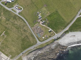 Oblique aerial view centred on the excavated broch and settlement at Old Scatness, Sumburgh, and the visitor attraction, taken from the NW.