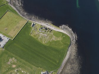 Oblique aerial view of the excavated settlement, broch and lairds house at Jarlshof, taken from the NNE.