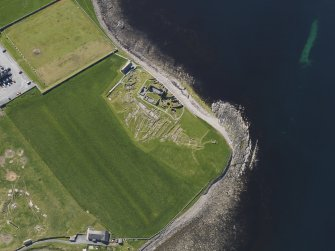 Oblique aerial view of the excavated settlement, broch and lairds house at Jarlshof, taken from the NNW.