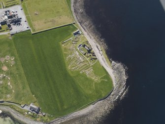 Oblique aerial view of the excavated settlement, broch and lairds house at Jarlshof, taken from the NW.