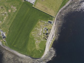 Oblique aerial view of the excavated settlement, broch and lairds house at Jarlshof, taken from the WNW.