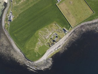 Oblique aerial view of the excavated settlement, broch and lairds house at Jarlshof, taken from the W.