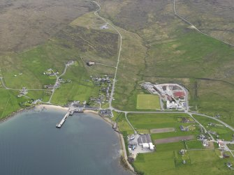 Oblique aerial view of Mid Yell centred on the pier, looking S.