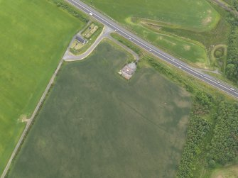 Oblique aerial view centred on the cropmarks of the barrow, round house and field boundaries, taken from the NNW.