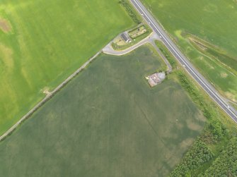 Oblique aerial view centred on the cropmarks of the barrow, round house and field boundaries, taken from the NW.