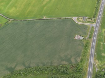 Oblique aerial view centred on the cropmarks of the barrow, round house and field boundaries, taken from the WNW.