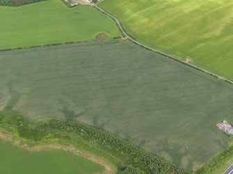 Oblique aerial view centred on the cropmarks of the barrow, round house and field boundaries, taken from the WSW.