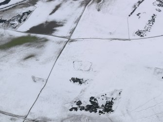 Oblique aerial view of the snow-covered remains of the settlement at Mire Loch, taken from the NE.