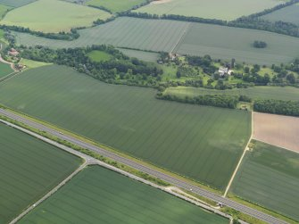 General oblique aerial view of the cropmarks of the possible quarries with Stevenson House in the distance, taken from the WSW.