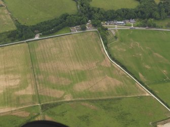 Oblique aerial view of the parchmarks of the enclosure and field boundaries with the church, burial ground and house adjacent, taken from the W.