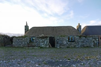 View of the East elevation of the thatched cottage at 13 Kilmoluaig, Tiree.