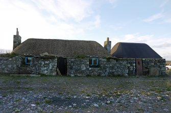 View of the East elevation of the thatched cottage and adjoining building at 13 Kilmoluaig, Tiree.