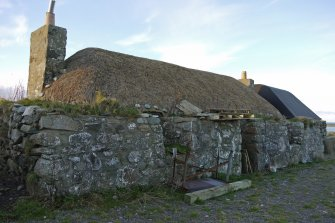 View of the East elevation of the thatched cottage and adjoining building at 13 Kilmoluaig, Tiree, taken from the South-East.