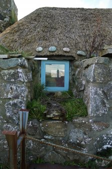 Detailed view of the Southern window to the East elevation of the thatched cottage at 13 Kilmoluaig, Tiree. The image shows the splayed window opening within the thick, battered wall. Stones tied to rope and 'chicken wire' can also be see above the window, which are for the purpose of keeping the thatching in place.