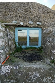 Detailed view of the Northern window to the East elevation of the thatched cottage at 13 Kilmoluaig, Tiree. The image shows the splayed window opening within the thick, battered wall. Stones tied to rope and 'chicken wire' can also be see above the window, which are for the purpose of keeping the thatching in place.