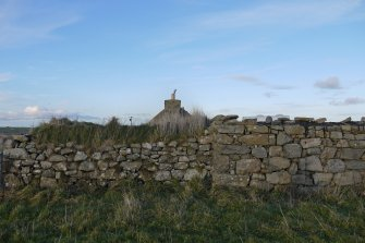 General view of the thatched cottage at 13 Kilmoluaig, Tiree, taken from the South. The remains of outbuildings are in the foreground with the Southern gable of the thatched cottage behind.