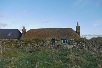 View of the West elevation of the thatched cottage at 13 Kilmoluaig, Tiree, taken from the West. The adjoining building to the North can also be seen to the left of the image.