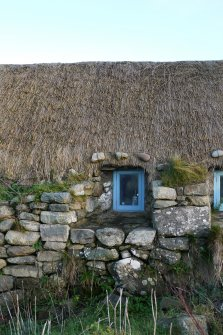Detailed view of the Northern window to the West elevation of the thatched cottage at 13 Kilmoluaig, Tiree. The image shows the splayed window opening within the thick, battered wall. Stones tied to rope and 'chicken wire' can also be see above the window, which are for the purpose of keeping the thatching in place.