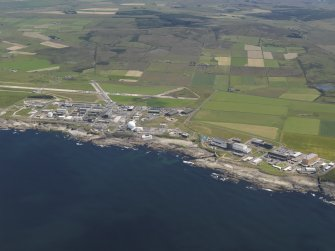 General oblique aerial view of the Dounreay Nuclear Research Facility with the airfield beyond, taken from the NW.