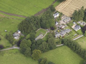 General oblique aerial view of the village centred on the church taken from the SSW.