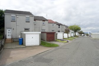 Street view showing partly terraced housing at Brick Row and Brewlands Avenue, Bo'ness, taken from the East. Each house is set back from the one before as they recede down the hill, and each has its own garage and direct access from the street. This photograph was taken as part of the Bo'ness Urban Survey to illustrate the character of the Hillcrest and Brewlands Area of Townscape Character.