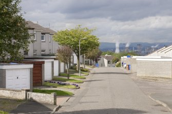Street view showing partly terraced housing at Brick Row and Brewlands Avenue, Bo'ness, taken from the East. Each house is set back from the one before as they recede down the hill, and each has its own garage and direct access from the street. Grangemouth can be seen in the distance to the centre of the image. This photograph was taken as part of the Bo'ness Urban Survey to illustrate the character of the Hillcrest and Brewlands Area of Townscape Character.