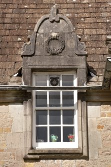 Detail of east dormer window with carved stone pediment at 1st floor level of south facade