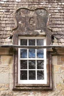 Detail of north dormer window with carved stone pediment at 1st floor level of east facade