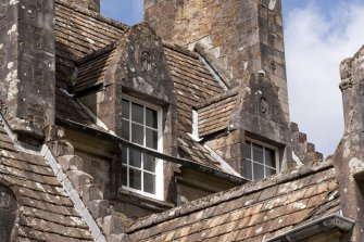 Detail of dormer windows with carved stone pediments on 2nd floor of east facade