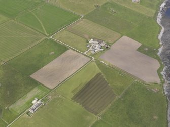 Oblique aerial view centred on the farmstead at East House, Burroughston, looking N.