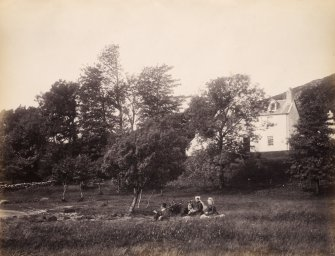 View of small group of figures situated in the grounds of the Manse near the shore of Lochawe with Kilchrenan Manse in the background, Lochawe, Argyll and Bute. Titled: '167. Kilchrennan Manse, 1871' PHOTOGRAPH ALBUM NO 186: J B MACKENZIE ALBUMS vol.1