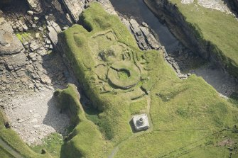 Oblique aerial view of Nybster Broch and Nybster Commemorative Monument, looking E.