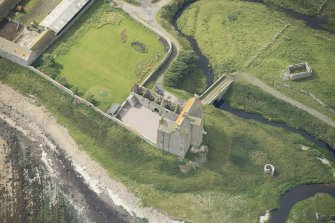 Oblique aerial view of Freswick Castle and bridge, looking SW.