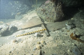 Timbers from a box-like structure photographed by the ADU in 1992. An intact mariner's compass was found beneath the timber in 1997, and the box elements may perhaps be parts of a second binnacle. Scale in centimetres. (Archaeological Diving Unit)