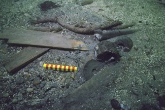 Another view of the excavated deposit in the collapsed stern interior showing at centre a wooden sheave and two pump-valves, and towards the top a length of served rope. Scale 15 centimetres. (Colin Martin)