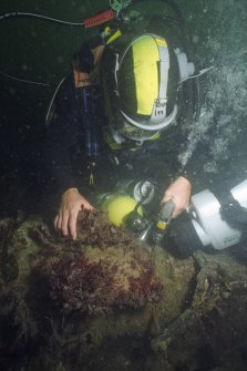 Dr David Gregory using a compressed-air drill prior to recording the concretion depth, corrosion potential, and pH value on a concreted cast-iron gun. (Colin Martin)