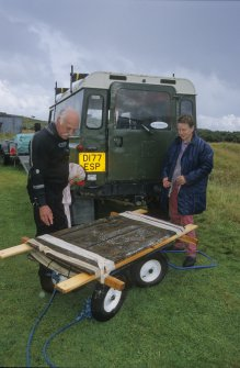 Dr Colin Martin and Jane Griffiths inspect a wooden panelled door (DP00/146) on a lifting-frame to which it is secured with bandages. It is ready to be loaded into a Land Rover for transport to a wet holding-tank. (Edward Martin)
