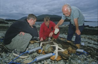 Brian Hession (left), Graham Scott, and Dr Colin Martin examine the recovered carriage (DP00/013) associated with Gun 8 (DP00/203). (Edward Martin)