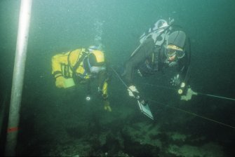 A pair of visiting divers tour the wreck, guided by a waterproof site-map. (Colin Martin)