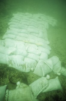 A skin of sandbags loosely filled with gravel laid over an exposed part of the wreck. (Colin Martin)