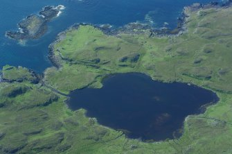 Aerial photograph of Loch na h-Airde from the NE, showing the canal, headland fort (extreme centre left) and the sheltered anchorage afforded by Sgeir Mhòr (top left). (Colin Martin)