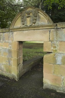 Entrance to garden at east end of house, showing decorated pediment.