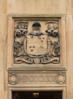 Detail of armorial panel and date above entrance on north front.