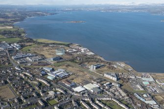General oblique aerial view of the Granton area of Edinburgh centred on the Gasworks, West Shore Road and the proposed site for the RCAHMS store with Cramond Island in the background, looking WNW.