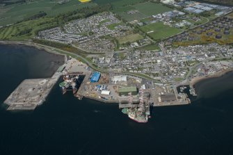 General oblique aerial view of Invergordon harbour and oil rig service base, looking N.