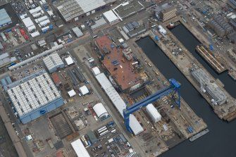 Oblique aerial view of Rosyth Naval Dockyard showing the construction of an aircraft carrier, looking ENE.